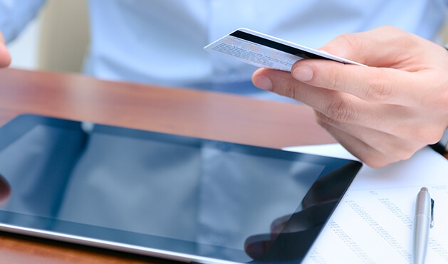 Photo of someone holding a credit card over a tablet.