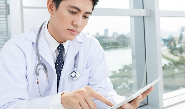 Photo of a doctor on a tablet device.